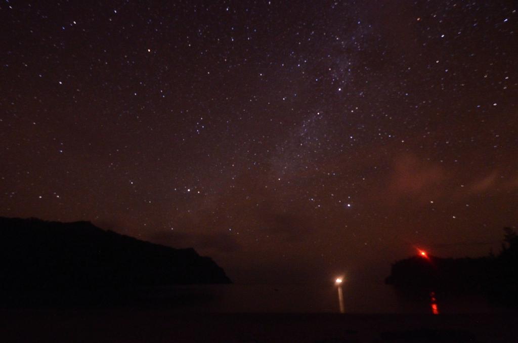 結露でぼやける。船の光(中心付近)と岬の灯台?のオレンジの光(右)が目立つ